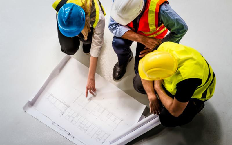 Three construction industry workers looking at plans
