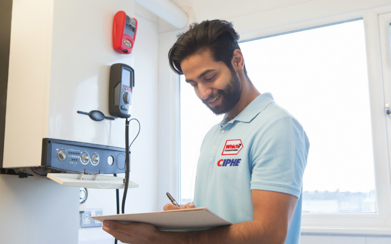 A heating engineer examining a boiler