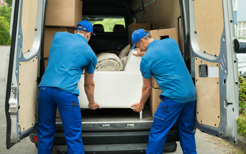 Two men loading furniture into a van