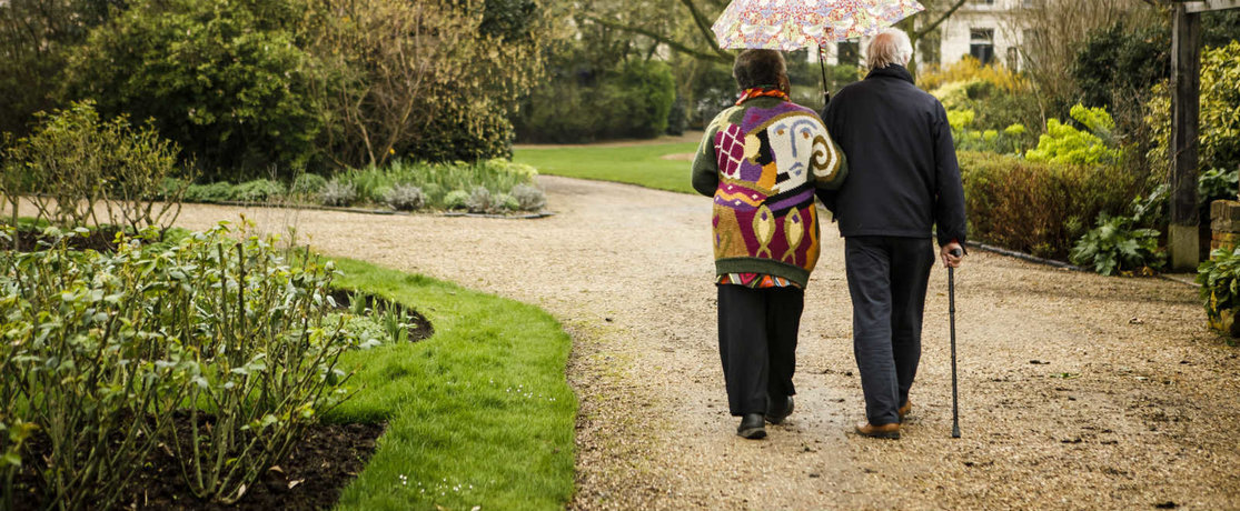 Two elderly people walking through a park