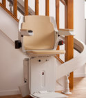 Square thumb acorn curved stairlift at bottom of staircase