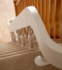Square thumb acorn curved rail along a staircase