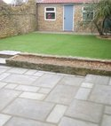 Square thumb indian sandstone patio and artificial grass installation   after