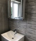 Square thumb textured grey tiles and vanity units in bathroom built by a1 gas ltd