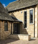 Square thumb cotswold stone house with aluminium clad front door